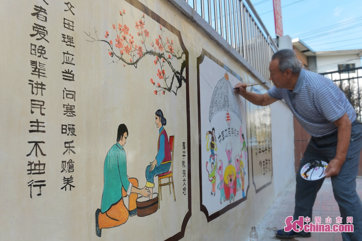 A painter paints on a wall on No.2 Yan&rsquo;an Road in Qingdao, a coastal city of east China&rsquo;s Shandong Province, Sept. 24, 2020. Main streets, walls and buildings in No.2 Yan&rsquo;an Road Community are decorated with calligraphy and colored drawing to celebrate the upcoming Mid-Autumn Festival and the National Day holiday. (Photo by Wang Haibin)<br/>