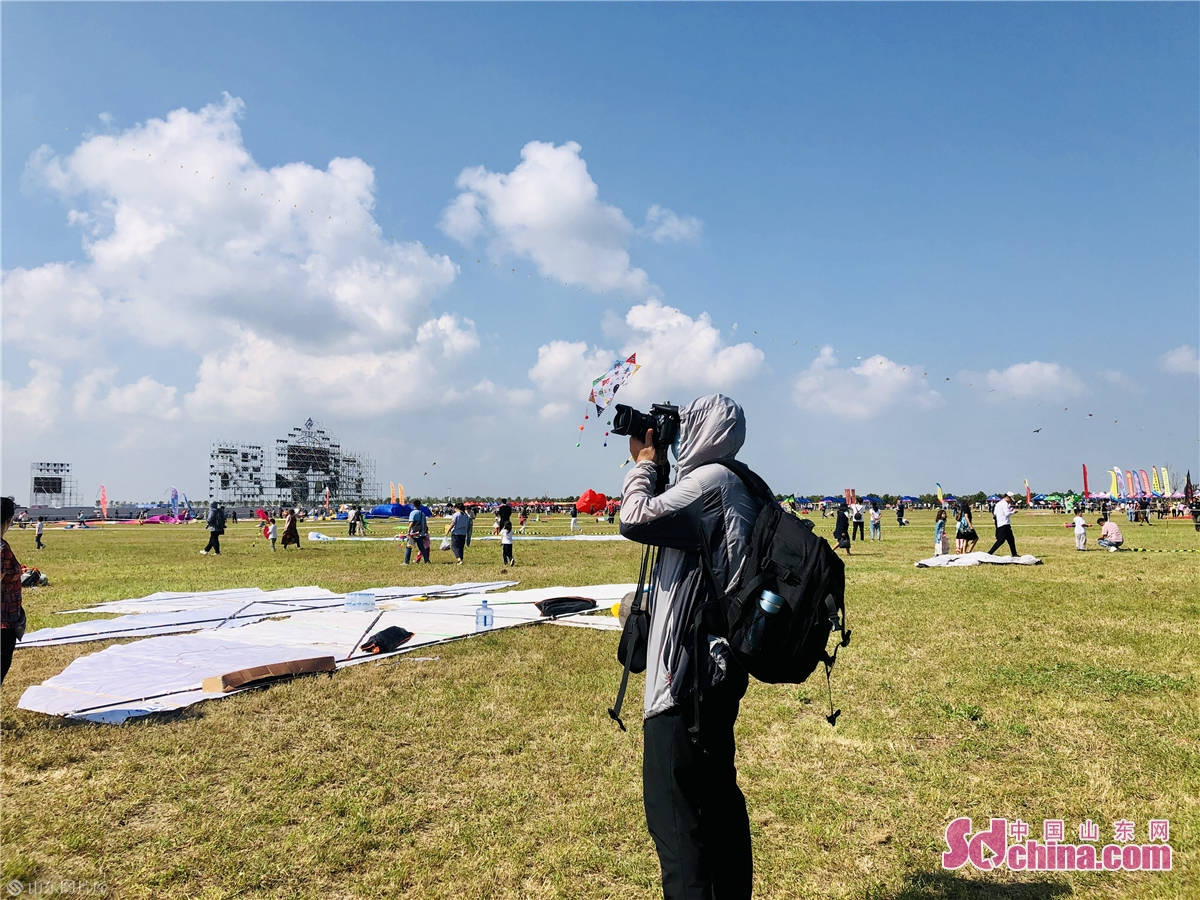 A photographer takes pictures at Binhai International Kite Flying Field in Weifang, east China&rsquo;s Shandong province on Sept. 26, 2020. The 37th Weifang International Kite Festival opened in Sept. 26, 2020 and will last till Oct. 8, 2020. (Sdchina/Han Beibei, Sun Xiaoru)<br/>