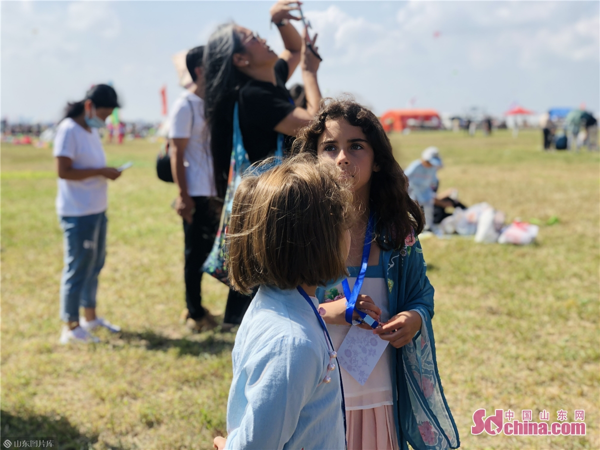 Two foreign children watch kite flying at Binhai International Kite Flying Field in Weifang, east China&rsquo;s Shandong province on Sept. 26, 2020. The 37th Weifang International Kite Festival opened in Sept. 26, 2020 and will last till Oct. 8, 2020. (Sdchina/Han Beibei, Sun Xiaoru)<br/>