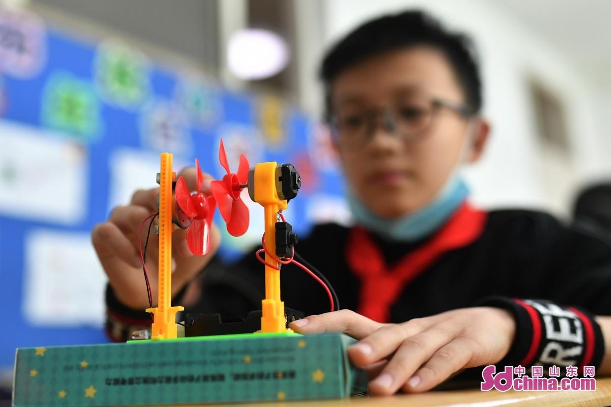 <br/>  在青岛市吉林路小学&ldquo;趣味科普课堂&rdquo;上,一名学生在调试风力发电机。<br/>