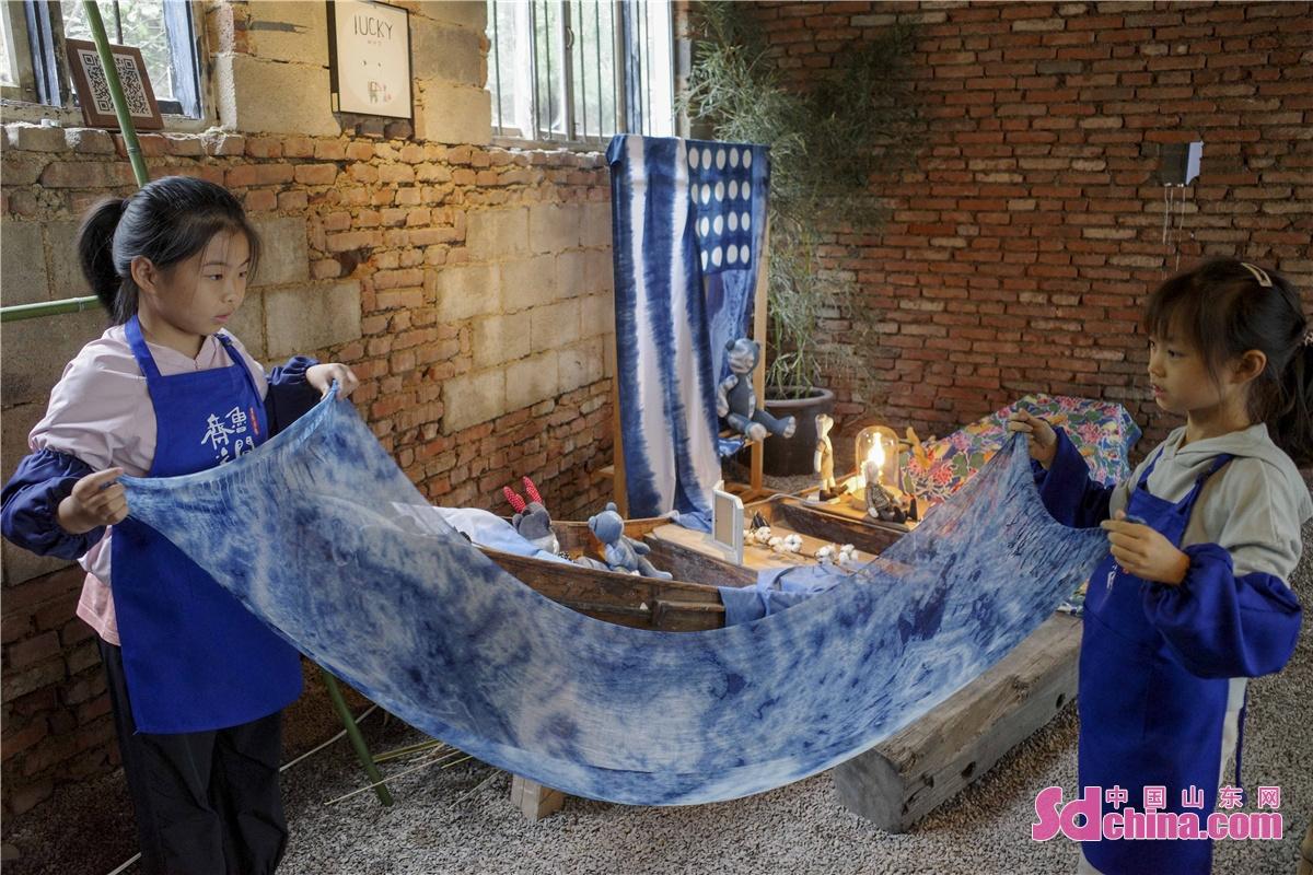 <br/>  每一条蓝染后的长巾,蓝与白交织,皆是体验的人们对生活的刻画、对文化印记的传承。这两个小学生的体验很投入。<br/>
