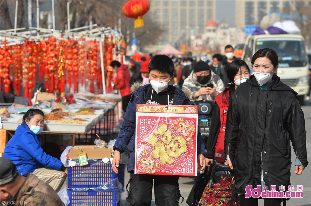 <br/>  2021年1月30日,在青岛市城阳年货大集上,一名小朋友将购买的福字挂于胸前逛街。<br/>