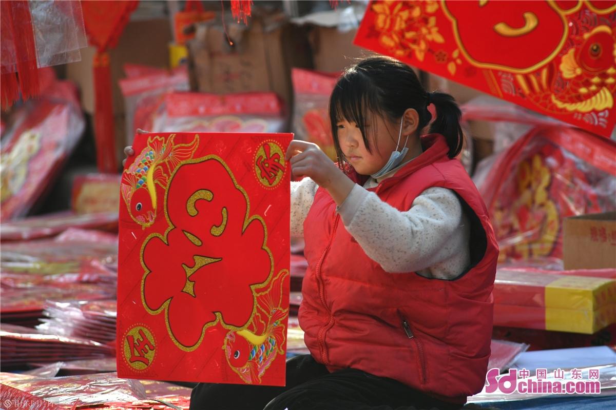 <br/>  2021年1月30日,一名休假的学生在青岛市城阳年货大集上协助父母销售春联。图为学生向顾客展示福字。<br/>