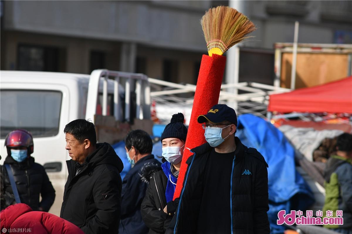 <br/>  2021年1月30日,在青岛市城阳年货大集上,市民带着购买的红毯逛街。<br/>