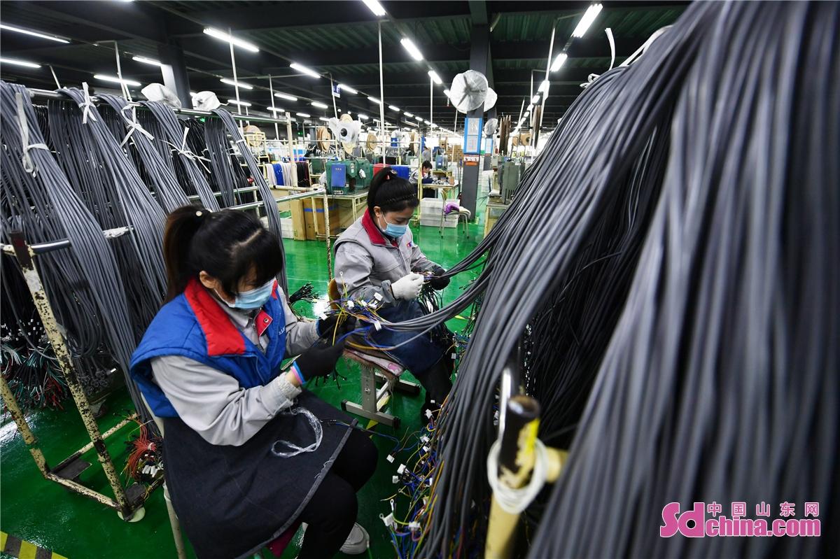 <br/>  2021年2月22日,位于青岛市城阳区惜福镇街道的悠进电装生产车间内,工人正在对产品进行外观检查。(王海滨 摄)<br/>