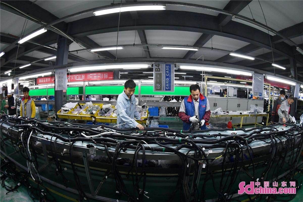 <br/>  2021年2月22日,位于青岛市城阳区惜福镇街道的悠进电装生产车间内,工人正在对产品进行外观检查。(王海滨 摄)