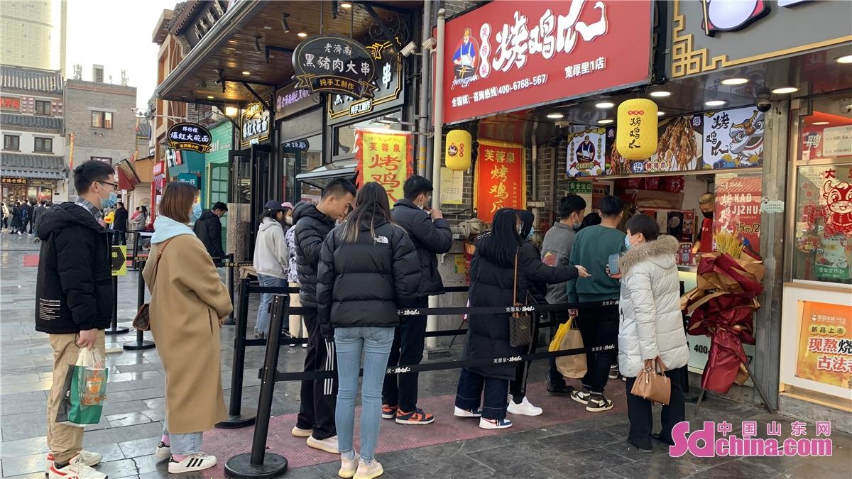 <br/>  游客在宽厚里排队买小吃。<br/>