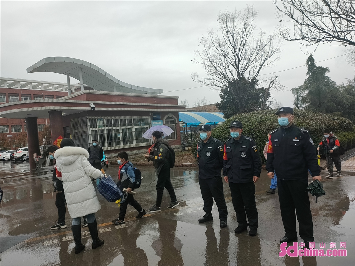 Police of Zaozhuang High-tech Zone guard students at a school gate to welcome their new semester in Zaozhuang, East China's Shandong province, March 1, 2021. Middle school and primary school students returned to school as scheduled for the spring semester in Beijing on Monday amid coordinated epidemic control efforts.<br/>