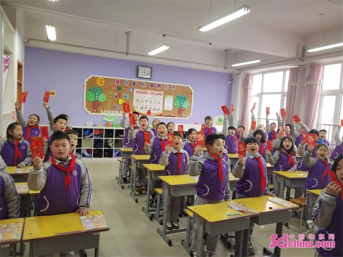 Students shows wish cards they have received on their first day of the new semester at Sangzi Primary School in Jinan, capital of East China's Shandong province, March 1, 2021. Middle school and primary school students returned to school as scheduled for the spring semester in Beijing on Monday amid coordinated epidemic control efforts.