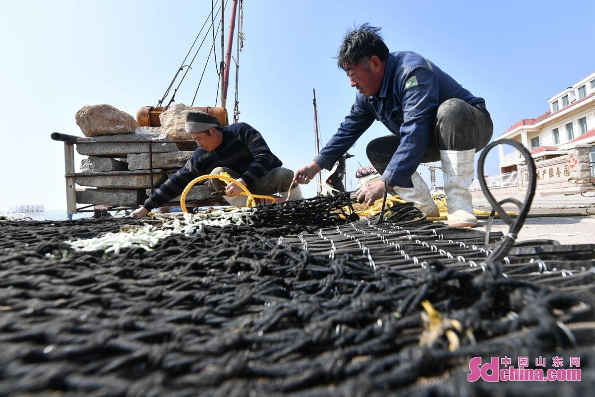 <br/>  工人在青岛市城阳区红岛街道一处渔港修补网具。