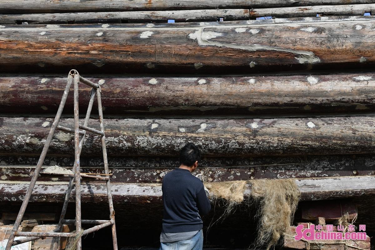 <br/>  工人在青岛市城阳区河套街道一处渔船维修厂为渔船补漏。<br/>