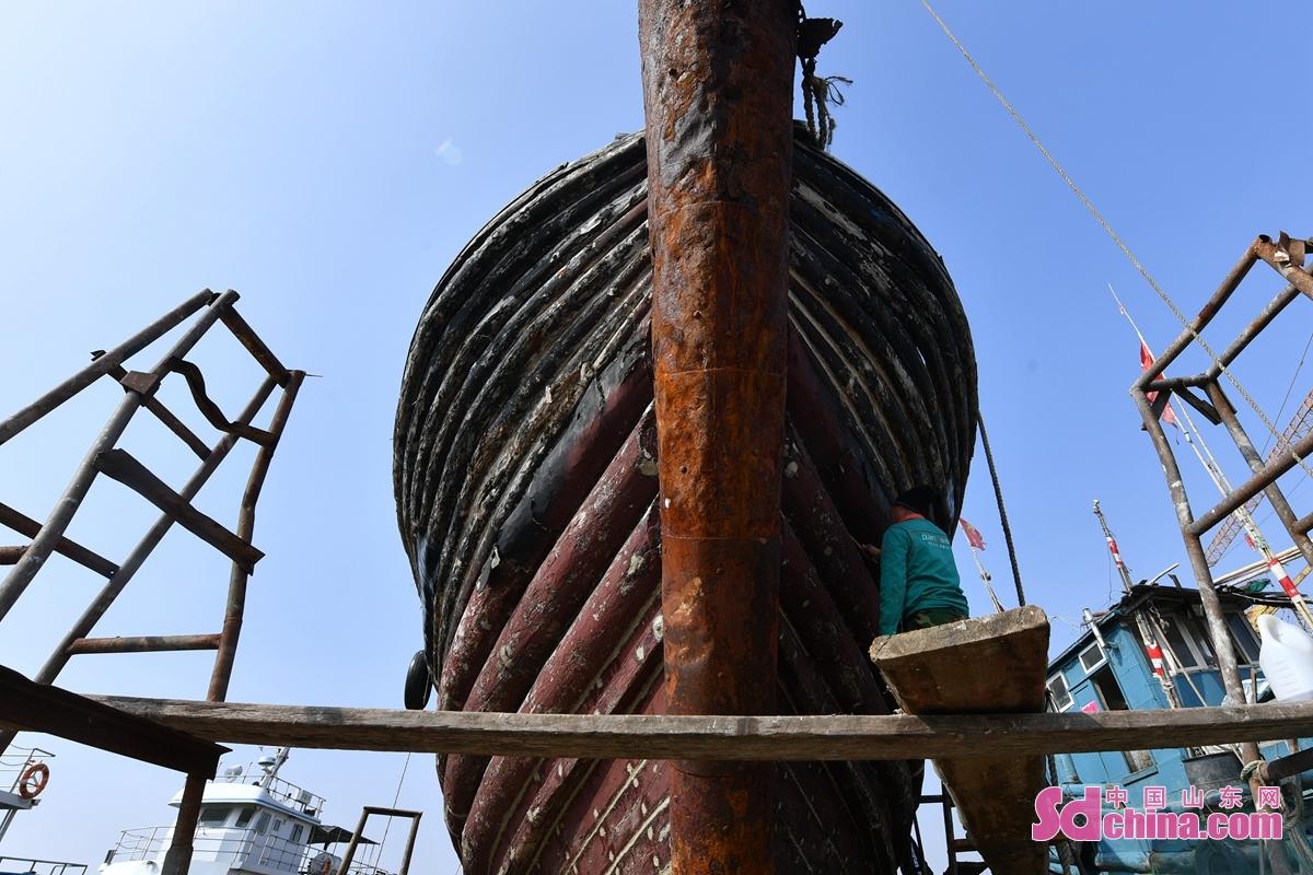 <br/>  春捕在即,工人在青岛市城阳区河套街道一处渔船维修厂修补渔船。<br/>