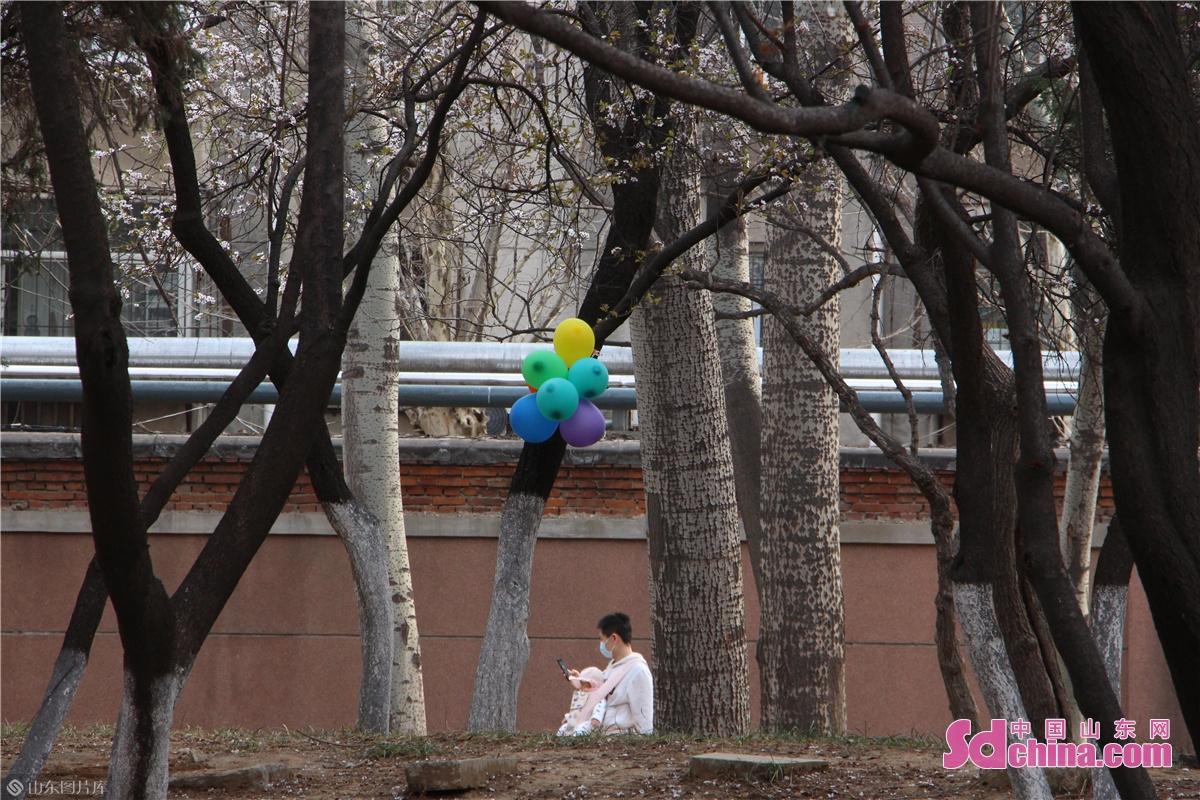 <br/>  一位市民带着孩子在公园内游玩。<br/>