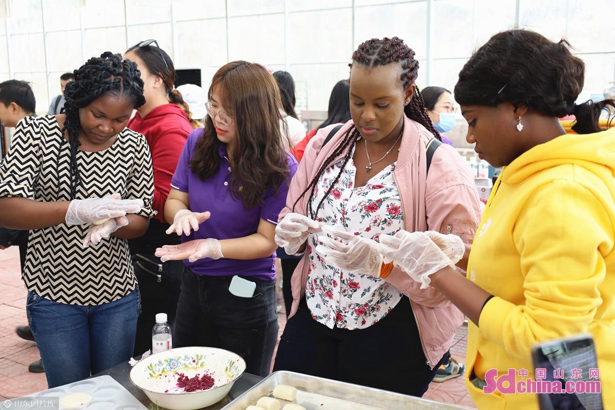 <br/>  国际学生在工作人员的指导下,按比例用白糖腌制玫瑰花瓣,并将馅料填入和好的面饼中,按压成型。<br/>