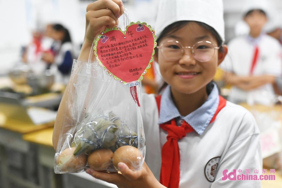 <br/>  一名青岛市明德小学的学生展示送给敬老院老人的&ldquo;爱心&rdquo;粽子和鸡蛋<br/>
