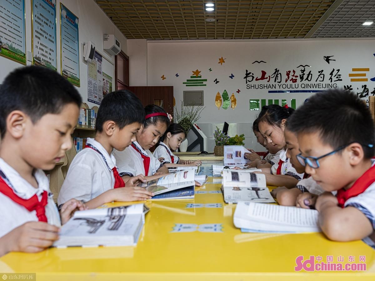 <br/>  6月11日,在日照市第三实验小学参加午间配餐的学生利用餐后时间阅读图书。<br/>