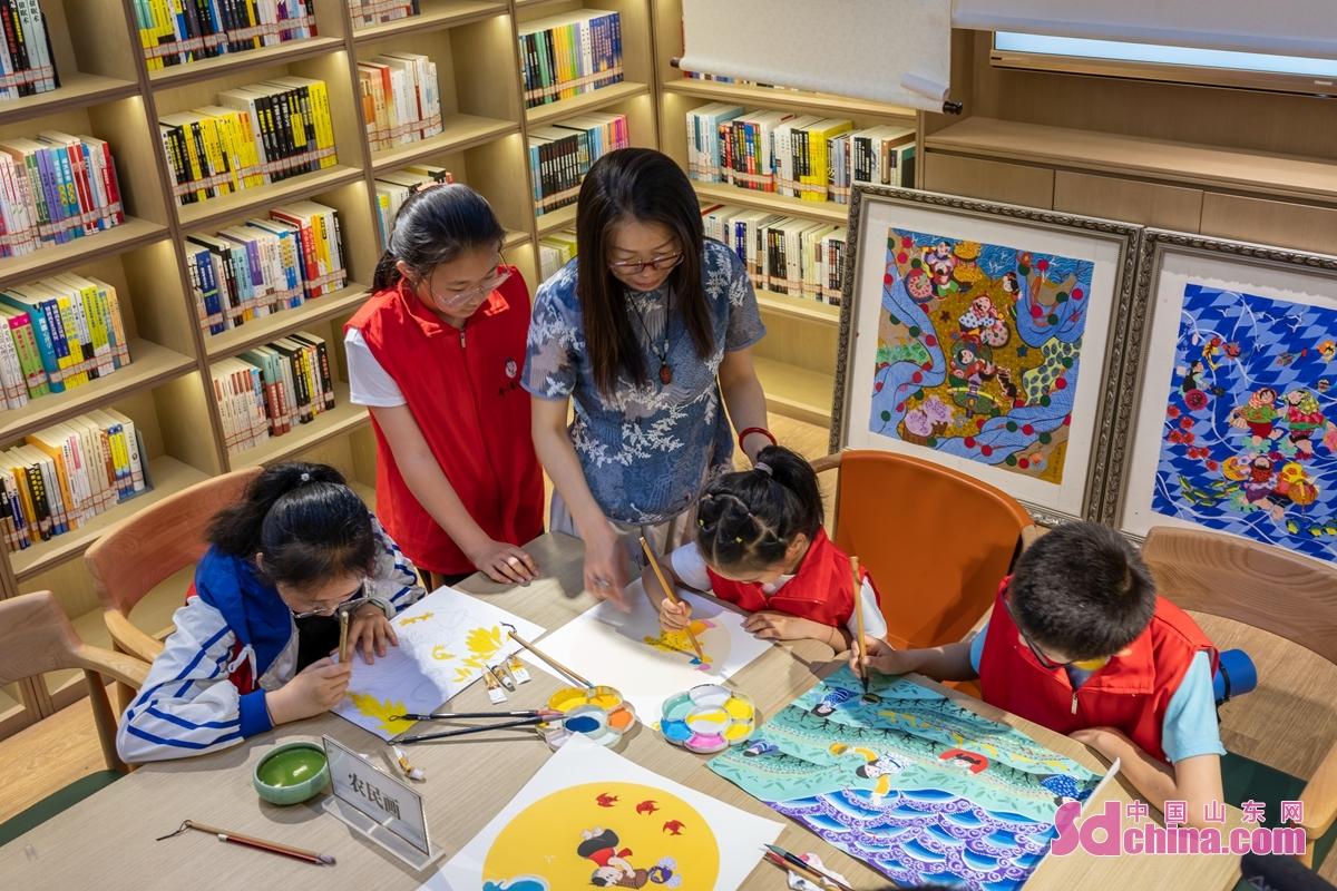 <br/>  在日照市东港区&ldquo;非遗&rdquo;展演现场,日照农民画省级传承人乔诺(左三)向小朋友传授农民画的绘画技法。<br/>