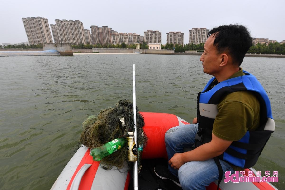<br/>  近日,青岛市城阳区野生动植物保护协会的志愿者在清理对潜鸟构成危害的网具时,遇到前段时间救助放归自然的鸬鹚,两只大鸟围绕志愿者的船只鸣叫靠近。野生动植物保护志愿者加大入海口湿地的巡查清理力度,确保候鸟安全度夏。图为青岛市城阳区野生动植物保护志愿者驾驶橡皮艇在白沙河入海口湿地巡查清理对潜鸟构成危害的网具。<br/>