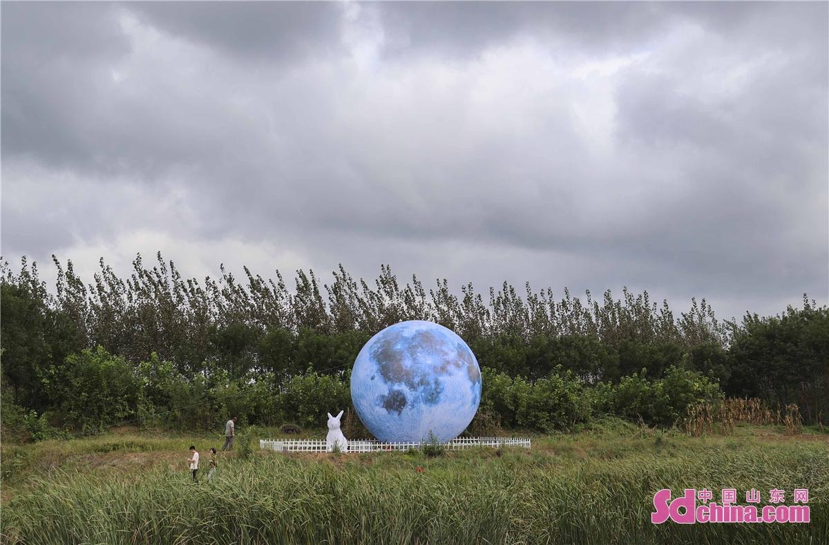 <br/>  2021年9月19日,青岛西海岸新区祝兹田园综合体鲁胶河畔,一个直径2米多的&ldquo;超级大月亮&rdquo;,矗立在河畔,辉映着六汪镇塔桥村,扮靓了&ldquo;两节&rdquo;期间美丽的田园,游人纷至沓来一睹为快。<br/>
