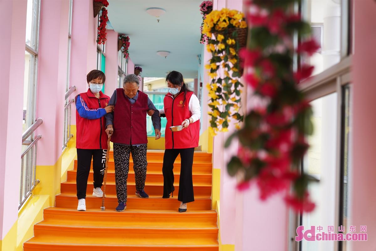 <br/>  2021年9月20日,山东省邹平市黄山街道新时代文明实践志愿者搀扶一名老人回房间。