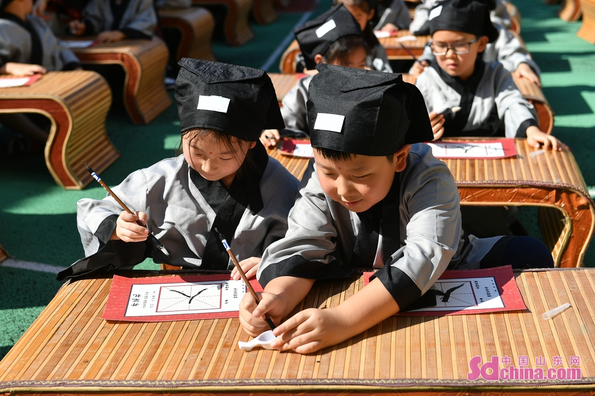 A first-writing ceremony was held for first-grade students at a primary school in Qingdao, east China's Shandong Province, Sept. 8, 2021. At the ceremony, students felt the charm of traditional culture by dressing up, paying homage to teachers and beating drums. (Photo by Wang Haibin)<br/>