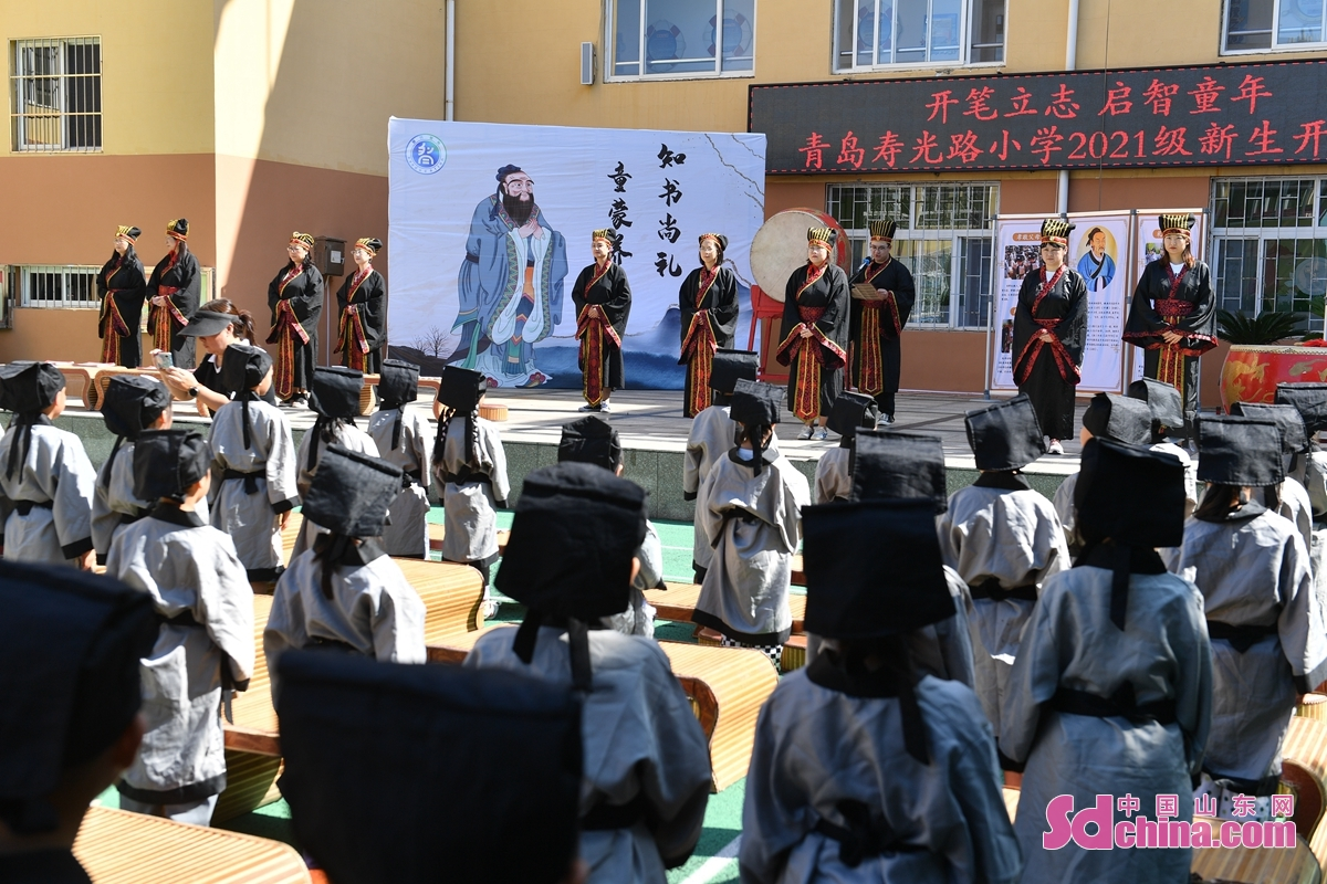 A first-writing ceremony was held for first-grade students at a primary school in Qingdao, east China's Shandong Province, Sept. 8, 2021. At the ceremony, students felt the charm of traditional culture by dressing up, paying homage to teachers and beating drums. (Photo by Wang Haibin)