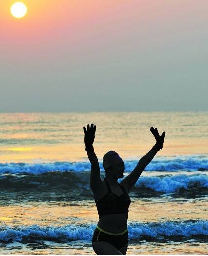 1月1日,万平口风景区海边,一位冬泳归来的女士向岸边的市民挥手致意