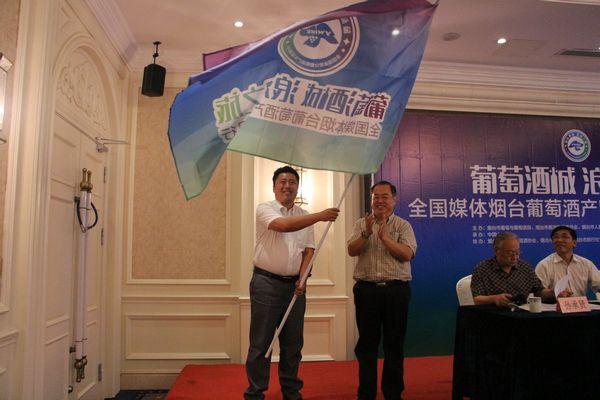 中共烟台市委宣传部常务副部长李明向采访团授旗