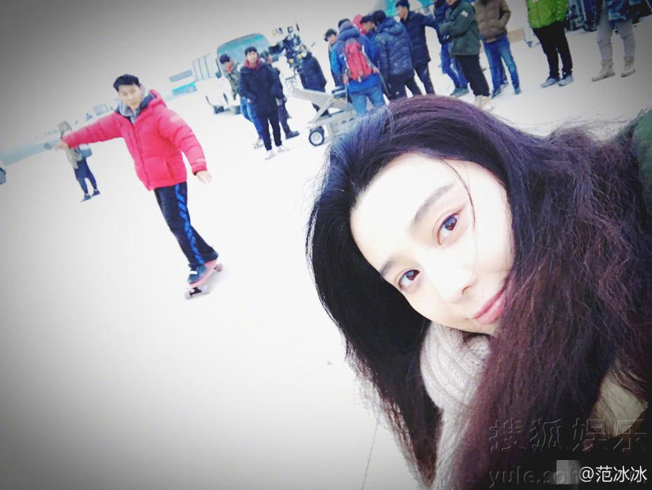 照片中,范冰冰素颜出镜,皮肤白皙,身后穿红衣的李晨则手舞足蹈。<br/>