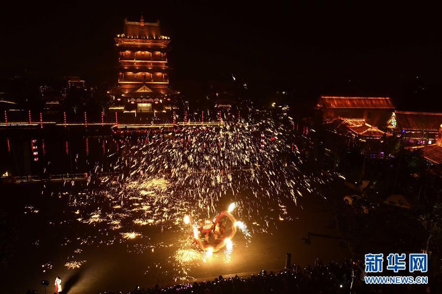 """12月30日晚,在山东省枣庄市台儿庄古城,民间艺人在表演""""火龙钢花""""。"""