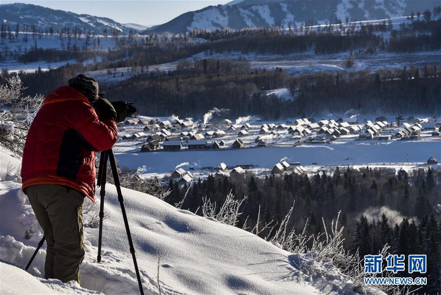 <br/>   白雪泼出&amp;ldquo;热&amp;rdquo;新年 1月2日,一名游客在拍摄晨曦中的禾木村。