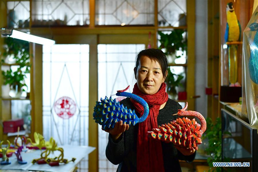 Cai Jianhua displays her paper sculptures at home in Zhengzhou, central China's Henan Province, Jan. 3, 2018. The 50-year-old Cai is a hearing impaired woman in Zhengzhou. After graduating from middle school, she learned embroidery, paper folding and weaving under her grandmother's instruction. As she became a laid-off worker in 2001, Cai showed an interest in paper sculpture. She innovated paper sculpture skills and won some prizes. In 2014, Cai Jianhua founded a paper sculpture workshop with the aid of a training center for disabled people and taught her skills to other disabled people. (Xinhua/Feng Dapeng)<br/>