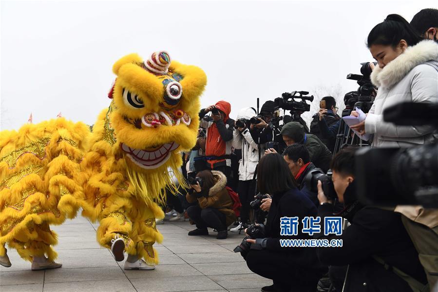 1月1日,在台儿庄古城开福门仪式上,舞狮艺人与游客互动。<br/>