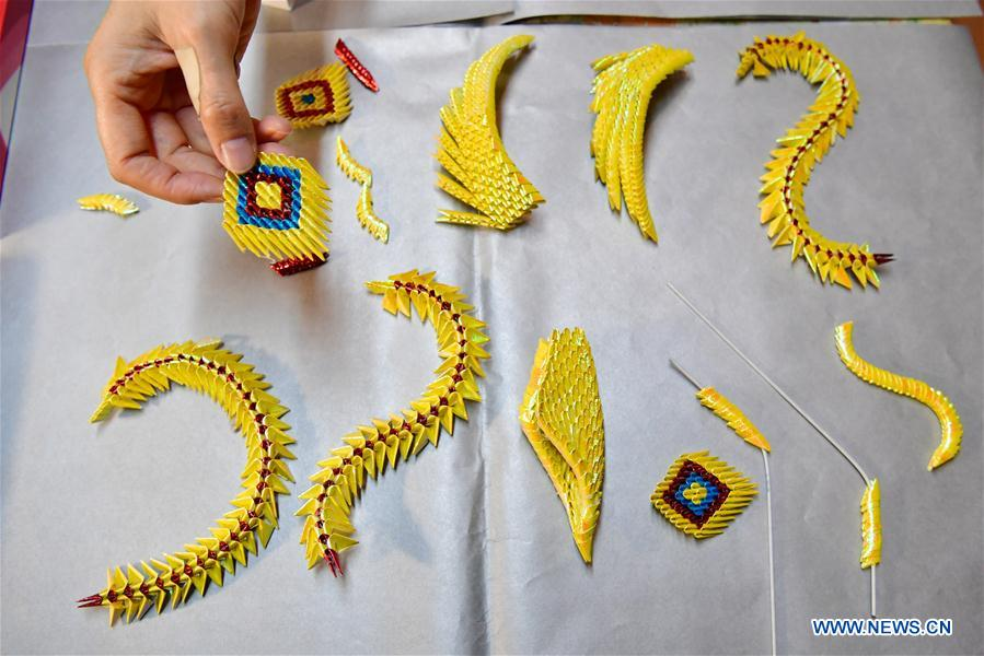 Cai Jianhua displays parts of her paper sculpture at home in Zhengzhou, central China's Henan Province, Jan. 3, 2018. The 50-year-old Cai is a hearing impaired woman in Zhengzhou. After graduating from middle school, she learned embroidery, paper folding and weaving under her grandmother's instruction. As she became a laid-off worker in 2001, Cai showed an interest in paper sculpture. She innovated paper sculpture skills and won some prizes. In 2014, Cai Jianhua founded a paper sculpture workshop with the aid of a training center for disabled people and taught her skills to other disabled people. (Xinhua/Feng Dapeng)<br/>