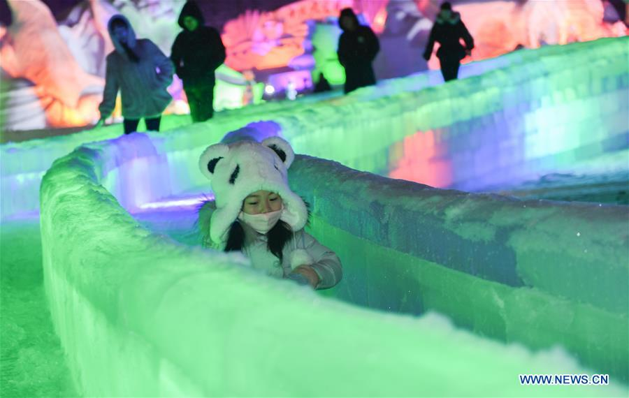 A girl plays in an ice and snow park in Arxan, north China's Inner Mongolia Autonomous Region, Jan. 7, 2018. The ice and snow sculptures here created a fantasy world and attracted a good many tourists. (Xinhua/Liu Lei)<br/>