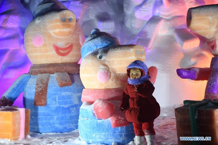 A child poses for photos with ice and snow sculptures in Arxan, north China's Inner Mongolia Autonomous Region, Jan. 7, 2018. The ice and snow sculptures here created a fantasy world and attracted a good many tourists. (Xinhua/Liu Lei)<br/>