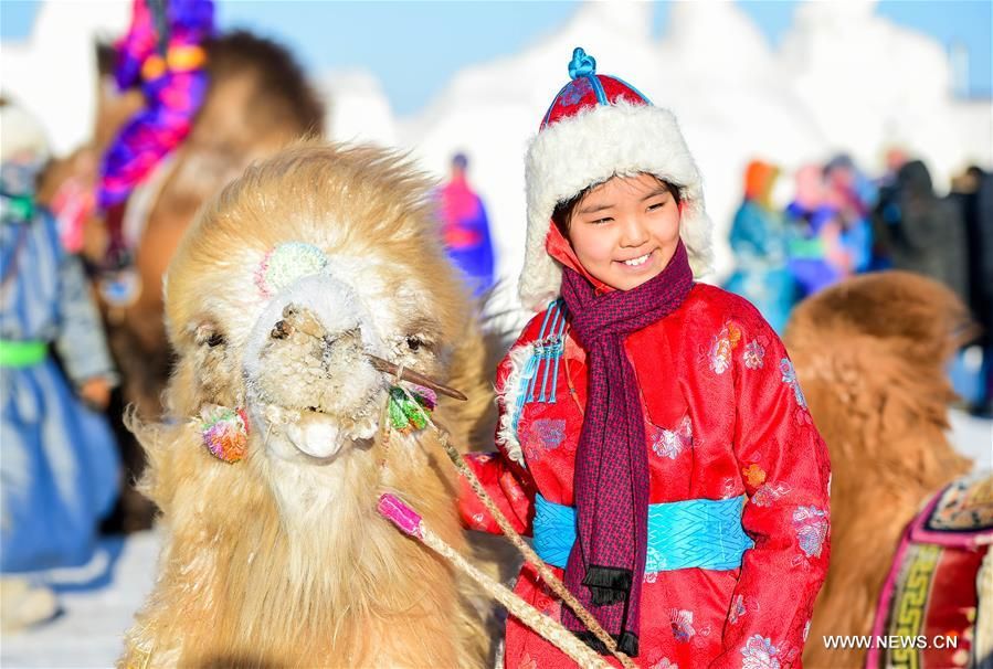 A girl of Mongolian ethnic group poses for photo with a camel in Sunite Right Banner, north China's Inner Mongolia Autonomous Region, Jan. 9, 2018. A camel fair, a local traditional festival including camel race and camel beauty contest, was held in the Banner on Tuesday. More than 200 camels took part in the fair. (Xinhua/Lian Zhen)<br/>
