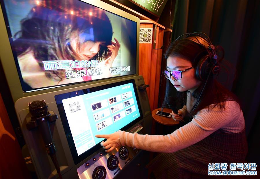 1월 10일, 여자 아이 한명이 시안 취장의 한 백화점에 설치한 미니 KTV에서 선곡하고 있다.