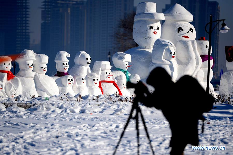 A photographer takes photos of snowman sculptures at an ice and snow park in Harbin, capital of northeast China's Heilongjiang Province, Jan. 11, 2018. Altogether 2,018 cute snowmen were displayed here to greet the year 2018. (Xinhua/Wang Kai)<br/>