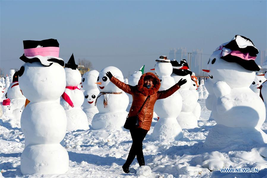 A tourist poses for photos with snowman sculptures at an ice and snow park in Harbin, capital of northeast China's Heilongjiang Province, Jan. 11, 2018. Altogether 2,018 cute snowmen were displayed here to greet the year 2018. (Xinhua/Wang Kai)<br/>