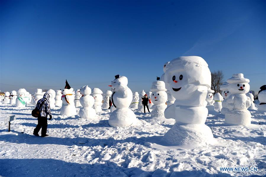 People watch snowman sculptures at an ice and snow park in Harbin, capital of northeast China's Heilongjiang Province, Jan. 11, 2018. Altogether 2,018 cute snowmen were displayed here to greet the year 2018. (Xinhua/Wang Kai)<br/>
