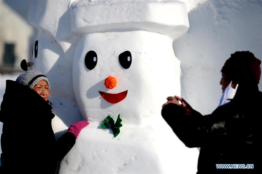 People pose for photos with snowman sculptures at an ice and snow park in Harbin, capital of northeast China's Heilongjiang Province, Jan. 11, 2018. Altogether 2,018 cute snowmen were displayed here to greet the year 2018. (Xinhua/Wang Kai)<br/>