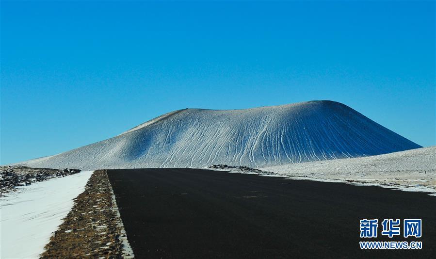 这是乌兰哈达火山群5号火山(1月13日摄)。<br/>  乌兰哈达火山群位于内蒙古自治区察哈尔右翼后旗乌兰哈达苏木与白音察干镇之间,20多座火山呈串珠状点缀在草原上。它们是在内蒙古高原南缘发现的全新世(距今1万年)有过喷发的唯一火山群。冬日里,皑皑白雪覆盖草原,火山熔岩地貌与雪原相映成辉,冰雪火山的奇妙身姿展露无遗。(新华社记者 彭源 摄)<br/>