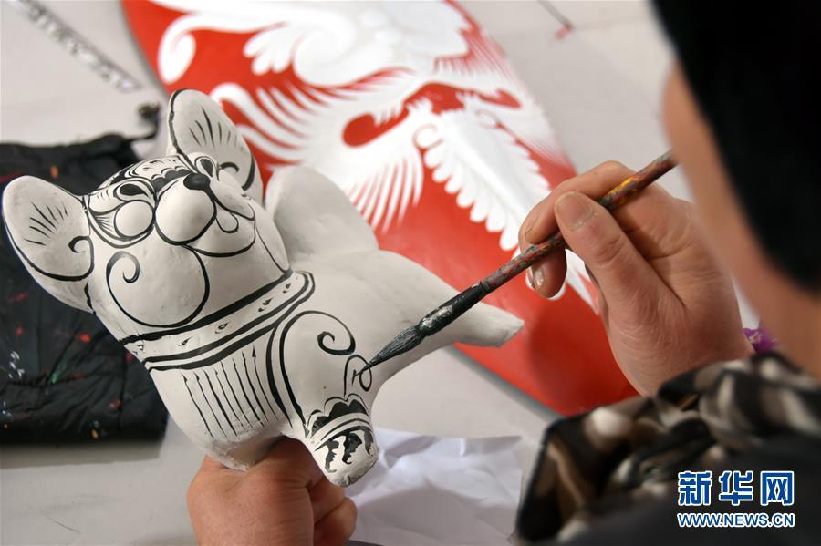 <br/>   1月11日,凤翔泥塑艺人在给一件泥塑狗作品描线。<br/>