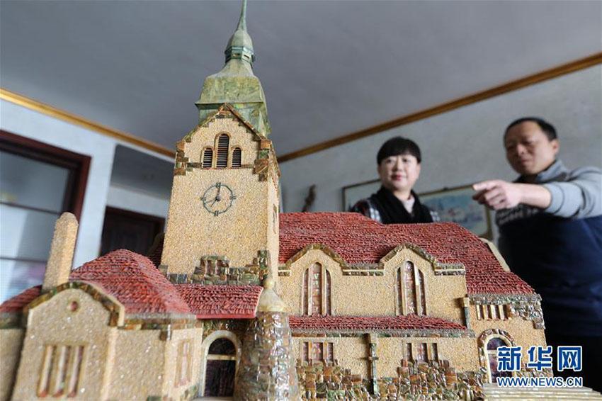 見学者に貝殻で作った建築物の模型を紹介する紀周統さん(1月14日、撮影・張進剛)。<br/>  山東省青島市に住む紀周統さんは貝殻を使った建築物の模型作りの虜になり、30年近く制作を続けている。紀さんは、貝殻をチップ状に加工したものを建築物の外壁の「煉瓦」として使用している。事前にデザインした図案にしたがって木製の中心部分にそれを張り付けていく方法で、青島の多くの古い建築物の模型を再現している。新華網が伝えた。(編集TK)<br/>
