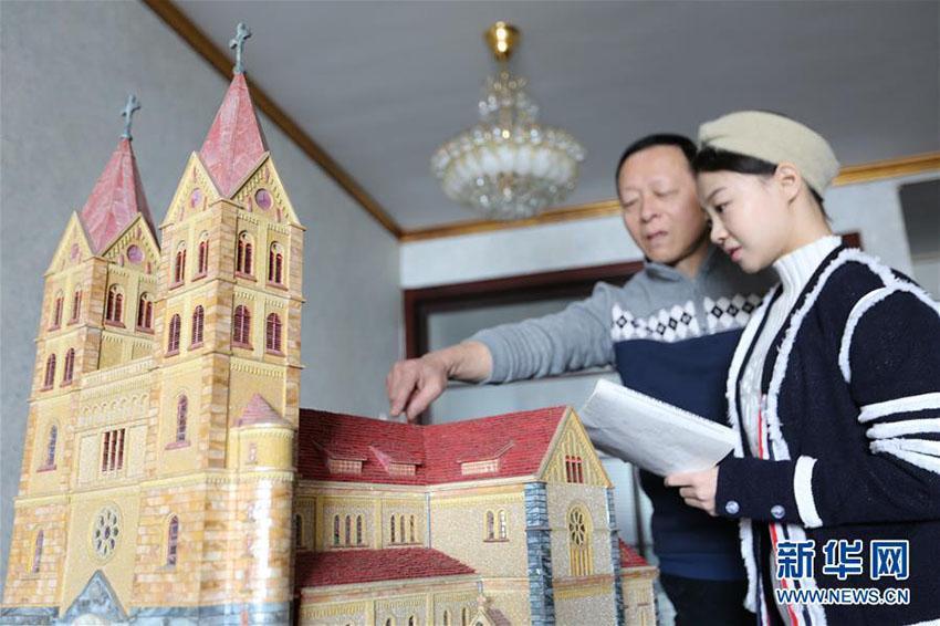 見学者に貝殻で作った建築物の模型を紹介する紀周統さん(1月14日、撮影・張進剛)。<br/>