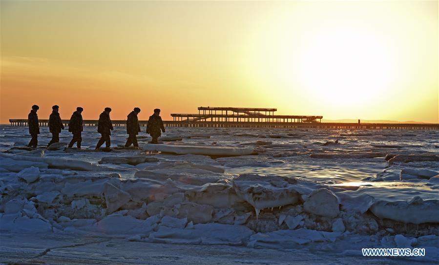 Staff members from Zhongxing border police station check the ice in Xingcheng City, northeast China's Liaoning Province, Jan. 16, 2018. Sea ice was formed along the Zhongxing Beach due to the low temperature. (Xinhua/Yang Qing)<br/>