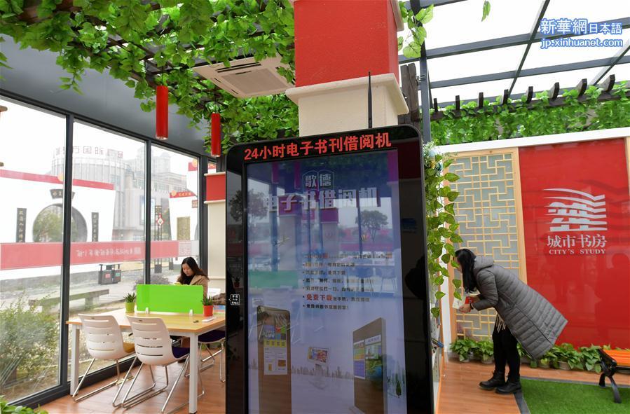 17日、24時間オープンのセルフサービス図書館で本を借りる市民。(新華社記者彭昭之撮影)<br/>  中国江西省南昌市初の24時間オープンのセルフサービス図書館がこのほど、青山湖区羅家鎮文化広場に正式にオープンした。この図書館の敷地面積は150平方メートル、蔵書冊数は8000冊以上で、電子書籍・雑誌の貸出機や紙媒体の書籍の貸出・返却手続きを行う設備が設置されている。市民は身分証明書を読み取らせることで図書館に入場できる。