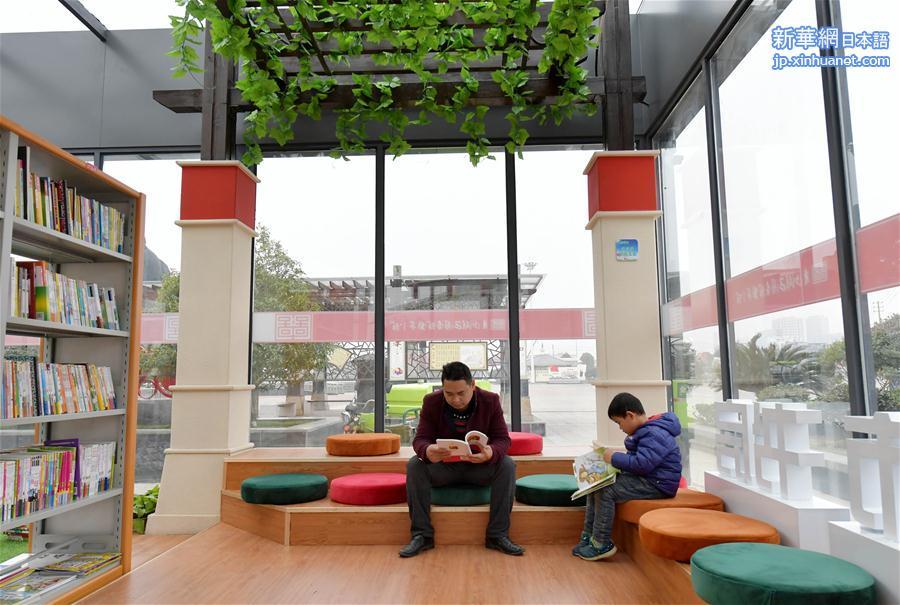 17日、江西省南昌市青山湖区羅家鎮の文化広場にある24時間オープンのセルフサービス図書館で本を読む市民。(新華社記者彭昭之撮影)<br/>  中国江西省南昌市初の24時間オープンのセルフサービス図書館がこのほど、青山湖区羅家鎮文化広場に正式にオープンした。この図書館の敷地面積は150平方メートル、蔵書冊数は8000冊以上で、電子書籍・雑誌の貸出機や紙媒体の書籍の貸出・返却手続きを行う設備が設置されている。市民は身分証明書を読み取らせることで図書館に入場できる。<br/>