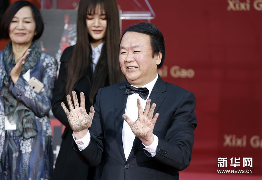 1月18日,在美国洛杉矶好莱坞TCL中国剧院,高希希在留印后展示双手。 中国导演高希希18日在美国好莱坞TCL中国剧院留下手印和脚印。新华社记者李颖摄<br/>